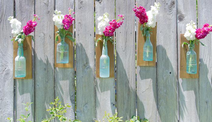 gartendeko ideen, vasen aus alten glasflaschen, weiße und rosa frühlingsblumen, diy anelitung
