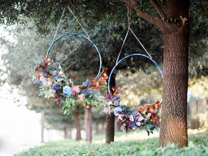 gartendeko selber machen, bäume dekorierne, blaue reifen, bunte blumen und zweigen