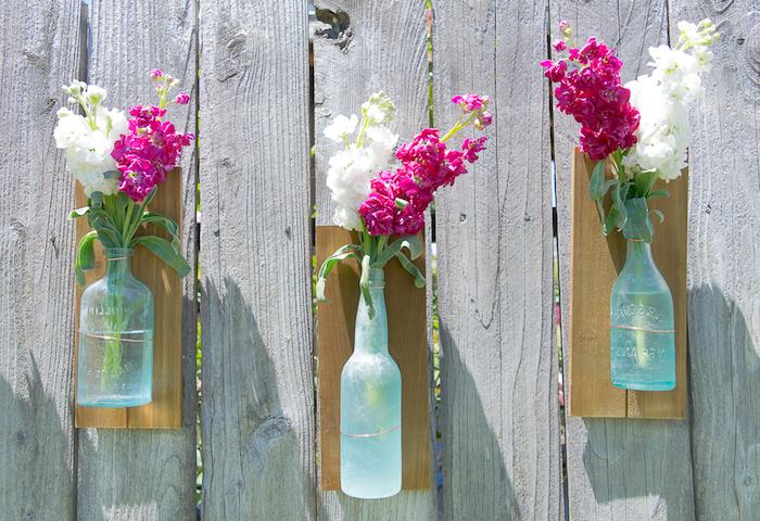 gartendeko selber machen, holzzaun dekorieren, upcycling glasfaschen, vasen mit blumen