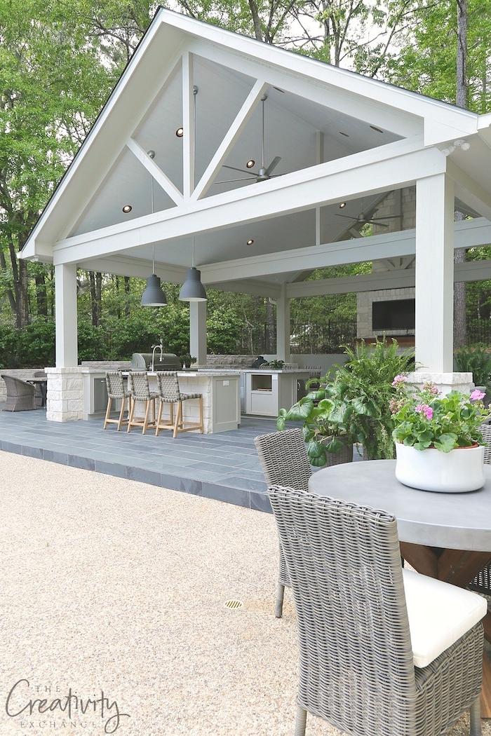 zwei graue stühle aus rattan und ein grauer tisch und ein weißer blumentopf mit violettenblumen und grünen blättern, ein weißes haus mit einer außenküche im garten