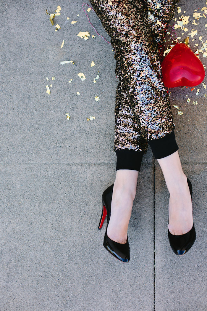 Hose mit Pailletten, schwarze High Heels, roter herzförmiger Ballon, goldenes Konfetti