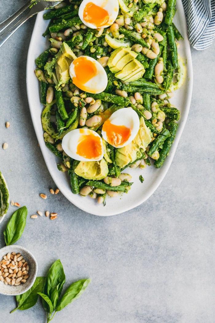 raffinierte Salate, Bohnen, kleine weich gekochte Eier in einer weißen länglichen Schale