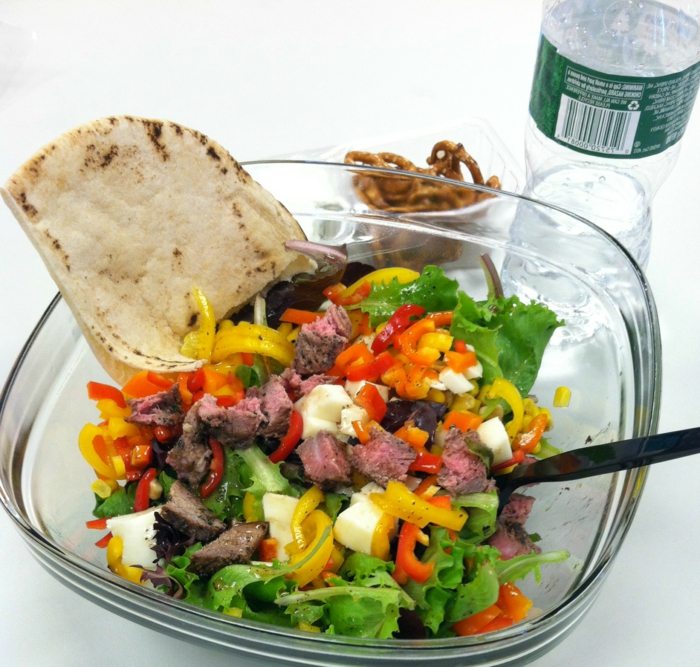 was ist gesunde ernährung, salatschüssel voll von grünsalat mit paprika, mozzarella, eier, tomaten und pitabrot als beilage