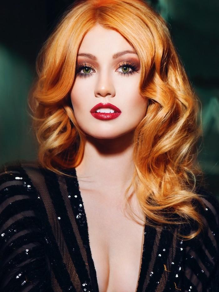 Katherine McNamara Haarfarbe, wellige Haare mit Mittelscheitel, roter Lippenstift und Smokey Eyes, schwarzes Kleid mit Pailletten