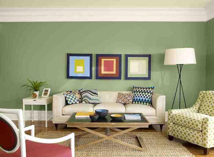 große grüne wand mit drei bildern mit blauen bilderrahmen und eine große weiße lampe, ein kleiner brauner tisch aus holz, ein sofa mit kissen, wohnzimmer streichen ideen