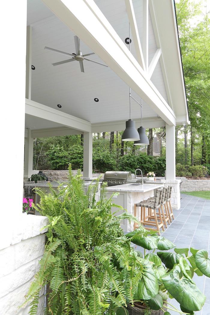 garten mit grünen pflanzen und bäumen, ein haus aus holz und eine außenküche mit grau8en lampen und stühle aus holz