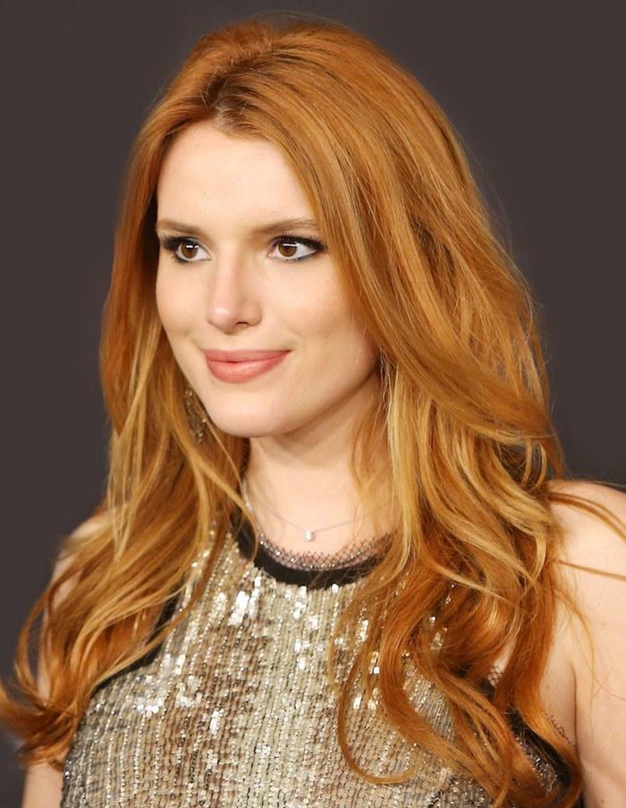 Kupferbraune Haare, matter Lippenstift und schwarzer Lidstrich, Kleid mit goldenen Pailletten und schwarzen Kanten