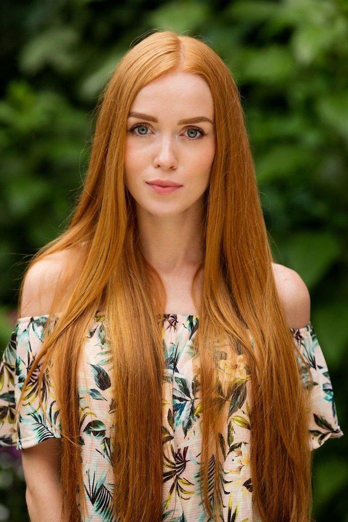 Lange kupferfarbene Haare mit Mittelscheitel, schulterfreies Top mit Blumenmuster