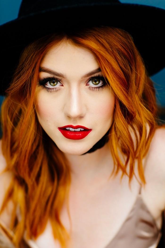 Katherine McNamara Haarfarbe Kupfer, grüne Augen, roter Lippenstift und schwarze Mascara, schwarzer Hut