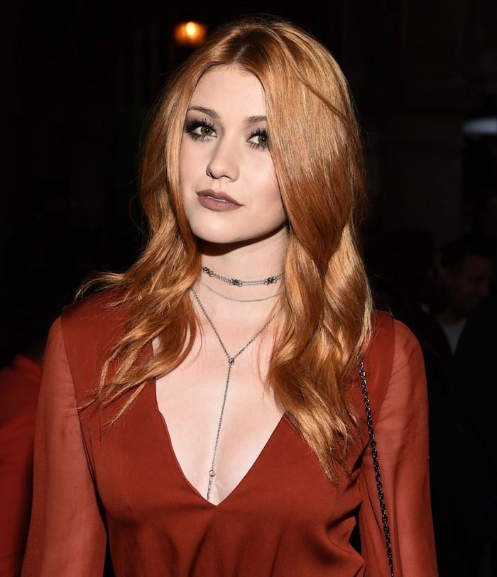 Kupferfarbene lange Haare mit Mittelscheitel, rotes Top mit V-Ausschnitt, matter Lippenstift und Smokey Eyes