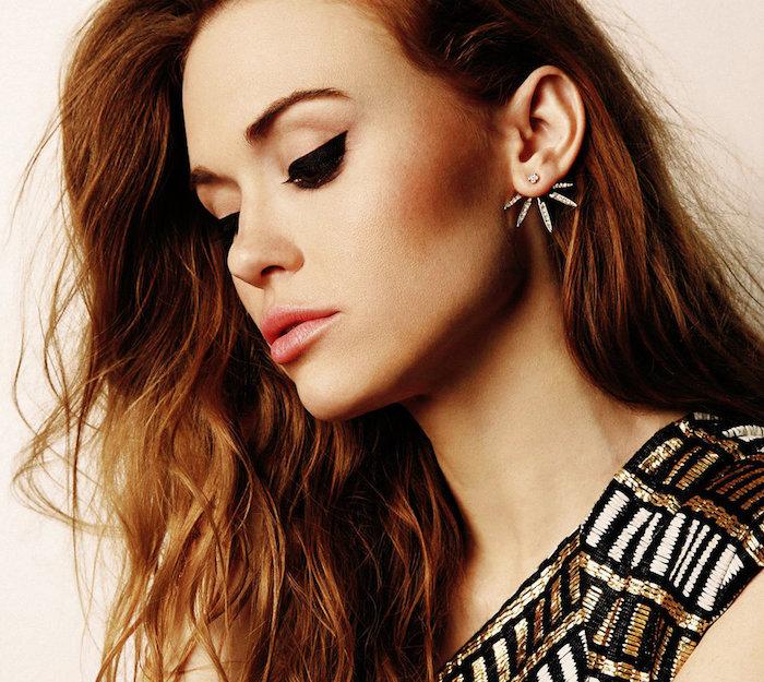 Kupferfarbene lange Haare und gebräunter Hautteint, schwarzer Lidstrich und rosafarbener Lippenstift, schwarzes Kleid mit goldenen Pailletten