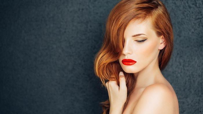 Lange kupferfarbene Haare mit Seitenscheitel, roter Lippenstift und schwarzer Lidstrich