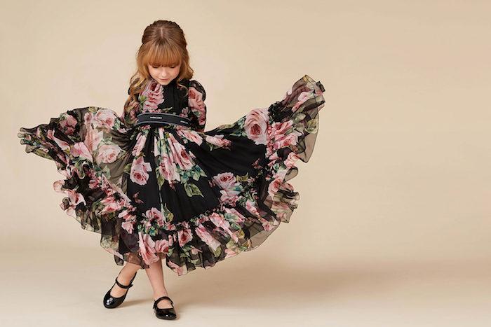 Halboffene Frisur, schöne Locken und gerader Pony, schwarzes Kleid mit Blumenmuster