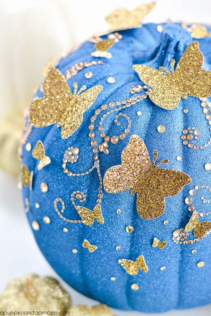 DIY Idee für Halloween Deko, Kürbis mit blauem Spray besprühen und mit kleinen goldenen Schmetterlingen verzieren
