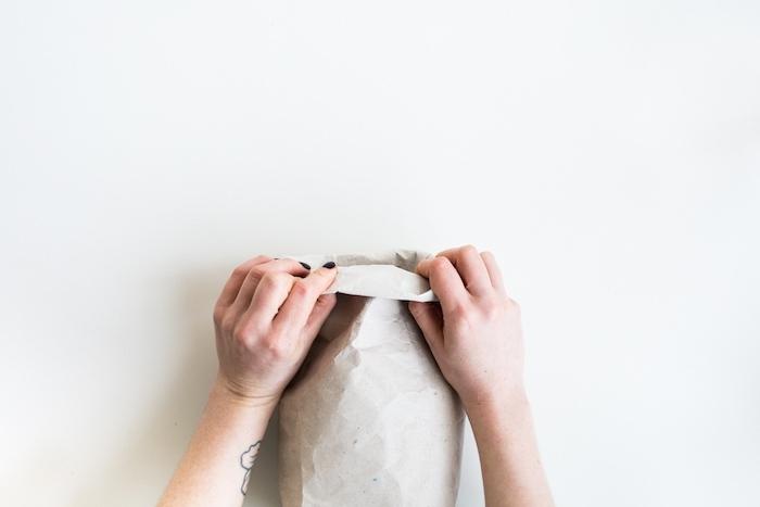 zwei hände mit einem schwarzen nagellack und eine gefaltete alte papiertüte, eine hand mit einem kleinen schwarzen tattoo am handgelenk