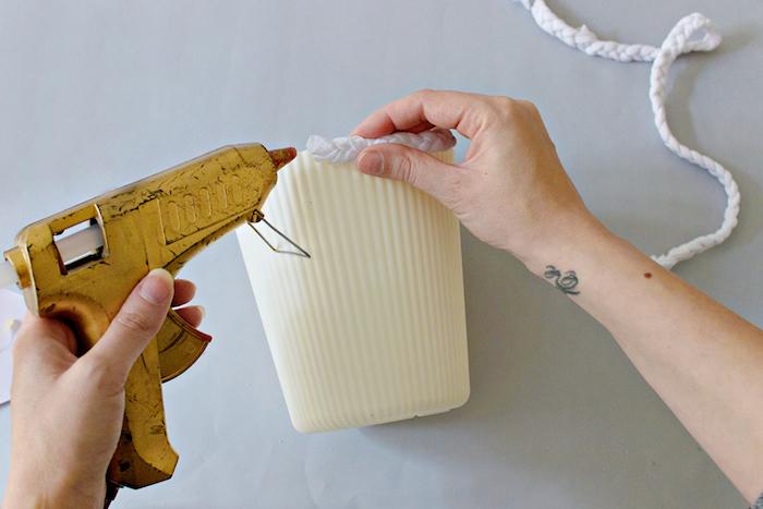 eine hand mit einem kleinen schwarzen tattoo am handgelenk und eine gelbe klebepistole und ein weißer blumentopf und lange streifen aus einem alten t-shirt