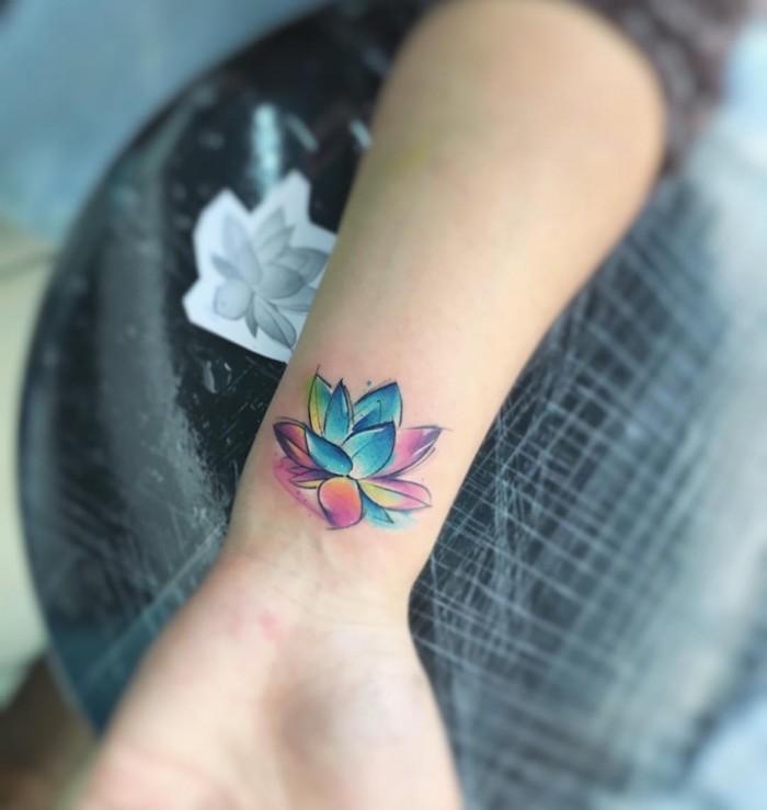hand mit einem kleinen bunten watercolor tattoo am handgelenk und mit einer kleinen bunten blume, frauen tattoo motive