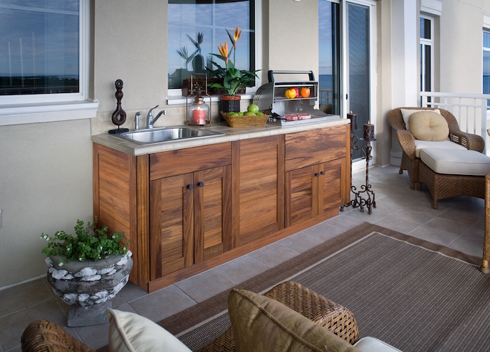 ein brauner teppich und ein blumentopf aus steinen und mit grünen pflanze, eine miniküche outdoor mit einem waschbecken
