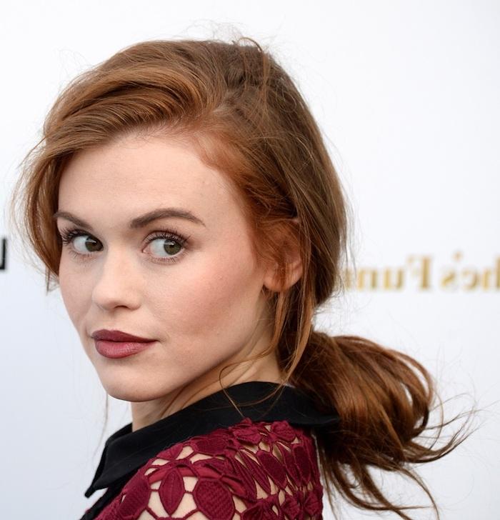 Kupferfarbene lange Haare, dunkelroter Lippenstift und schwarze Mascara, rotes Spitzenkleid mit schwarzem Kragen