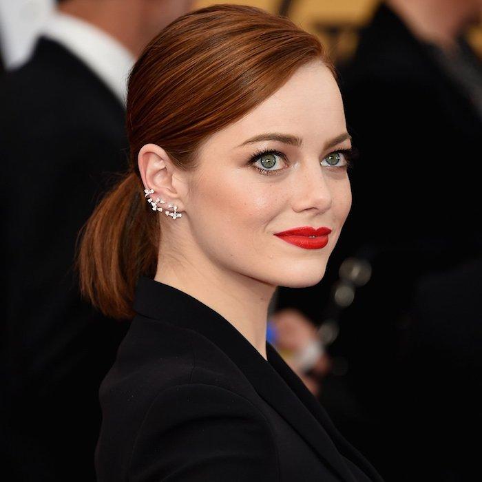 Mittellange kupferfarbene glatte Haare, grüne Augen und heller Hautteint, roter Lippenstift und schwarze Mascara