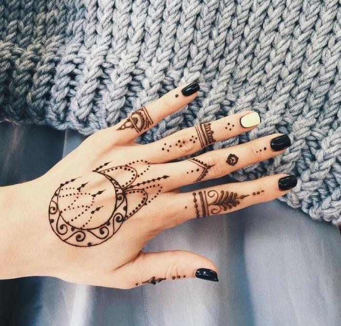 Schwarzes Henna Tattoo an der Hand, schwarzer Nagellack, ein weißer Nagel