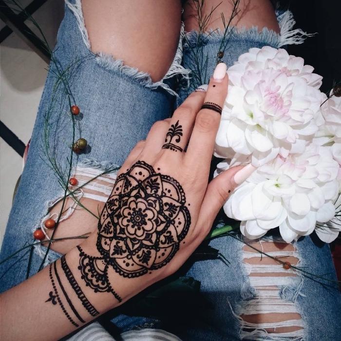 Schwarzes Henna Tattoo an der Hand, Mandala Blume, weißer Nagellack, weiße Chrysanthemen