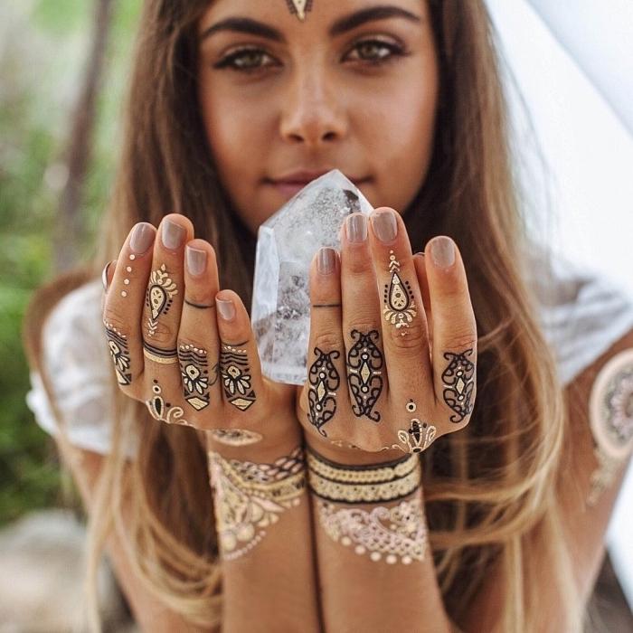 Schwarze und goldene Henna Tattoos an beiden Händen, Nude-Nagellack