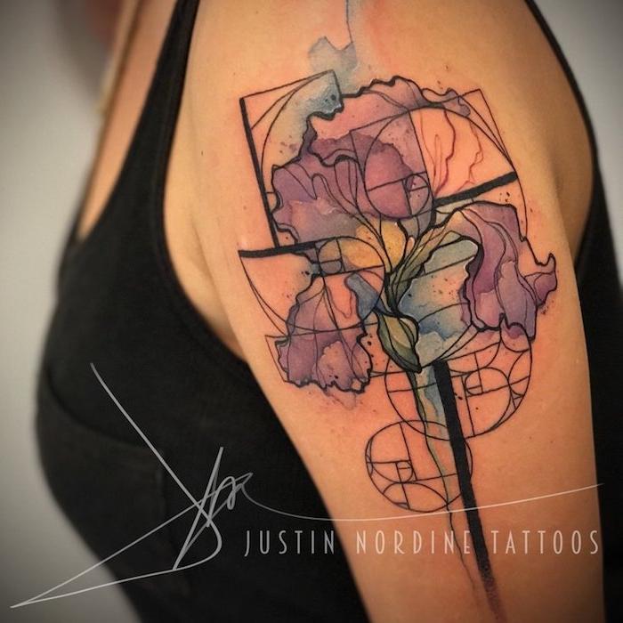 frau mit einem schwarzen unterhemd und mit einer hand mit einem tattoo arm mit blauen und violetten blumen