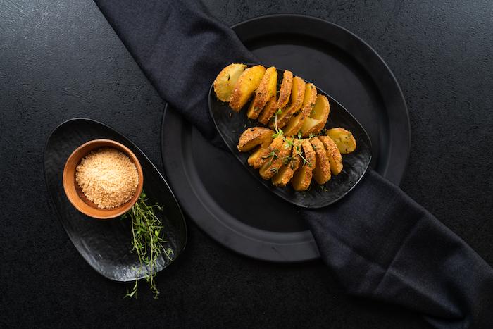 Hasselback Kartoffeln backen, mit Parmesan bestreuen, mit frischem Thymian servieren