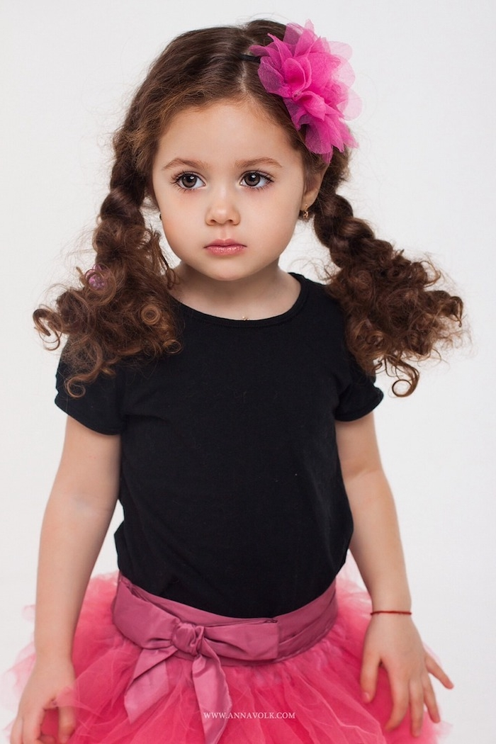 Lange braune Haare, zwei Zöpfe, violette Haarblüte, schwarzes Shirt und violetter Tüllrock