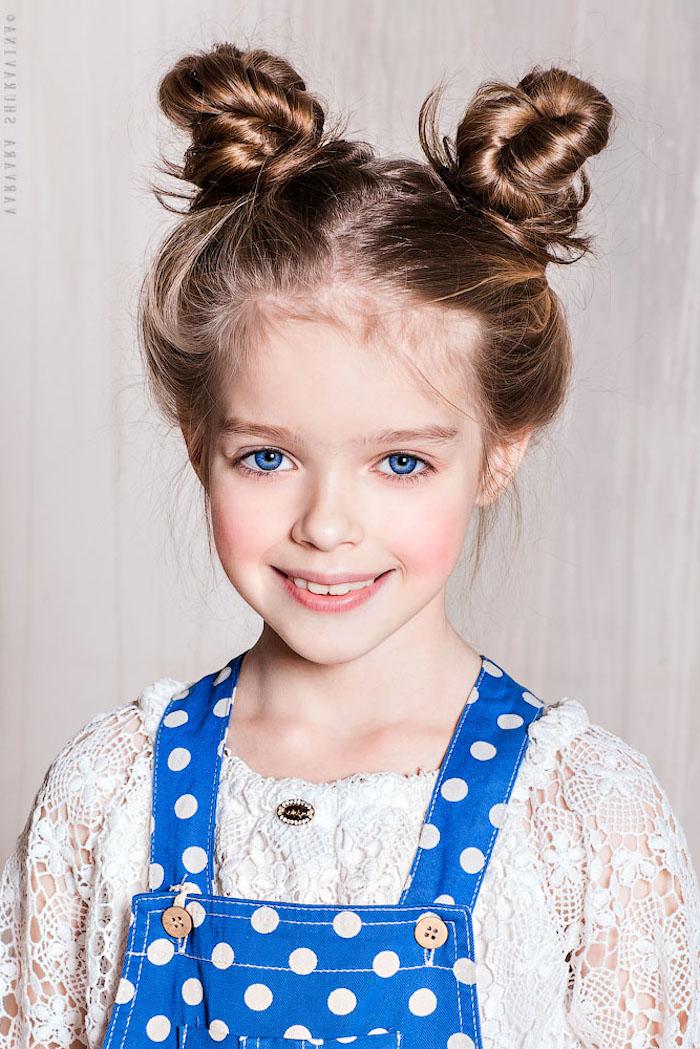 Double Bun, lässige alltägliche Frisur für Mädchen, weiße Spitzenbluse und blauer Jumpsuit, blaue Augen