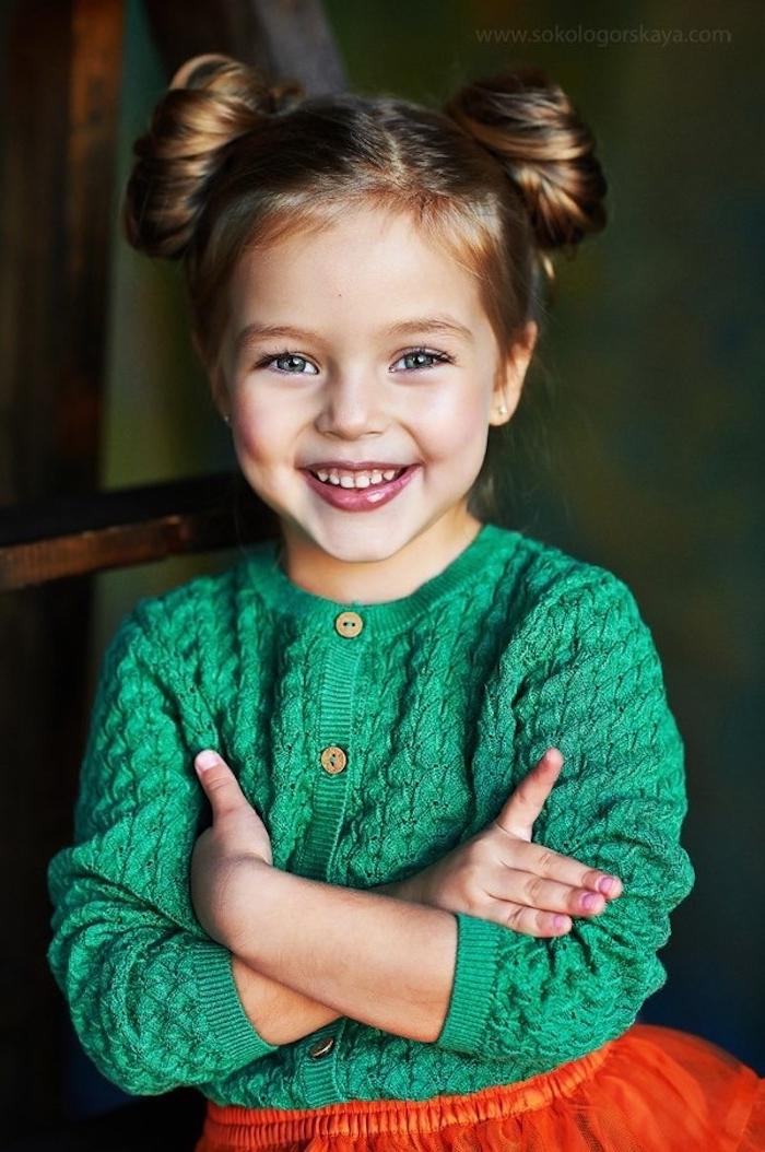Double Bun, grüne Strickjacke und roter Tüllrock, süßes Mädchen mit blauen Augen und dunkelblonden Haaren