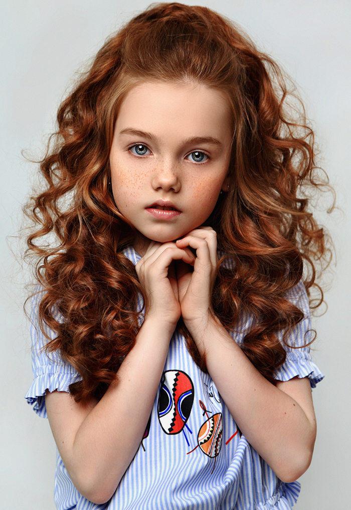Lange lockige rote Haare, halboffene Haare, blaue Augen, gestreifte Bluse mit bunten Applikationen