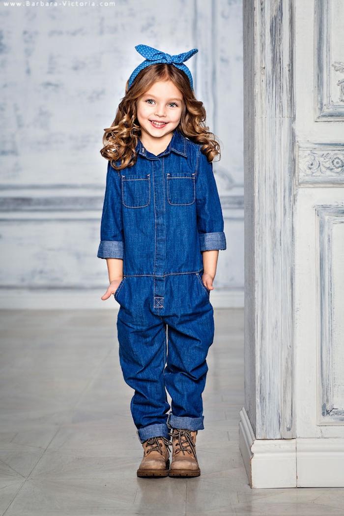 Schönes Mädchen mit welligen dunkelblonden Haaren und blauen Augen, Denim Jumpsuit und blaues Haarband