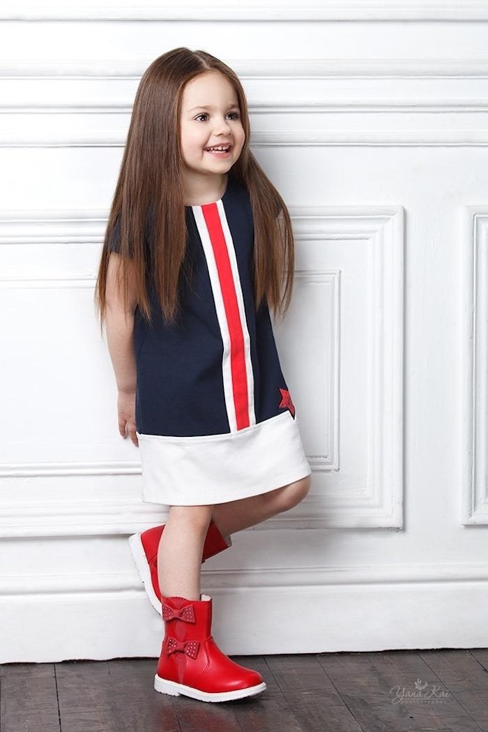 Lange glatte Haare mit Mittelscheitel, dunkelblaues Kleid mit roten und weißen Kanten, rote Stiefel mit Schleifen