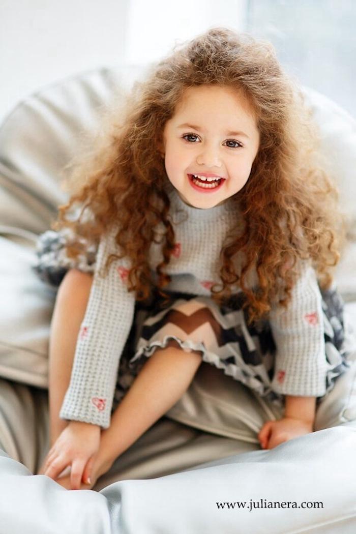 Schöne Kinderfrisuren, halboffene lange lockige Haare, graue Bluse mit langen Ärmeln