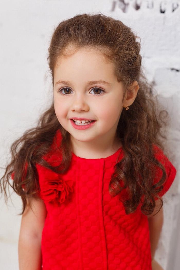 Braune halboffene Haare, braune Augen und heller Hautteint, knallrotes Kleid ohne Ärmel, Kindermode und Frisuren
