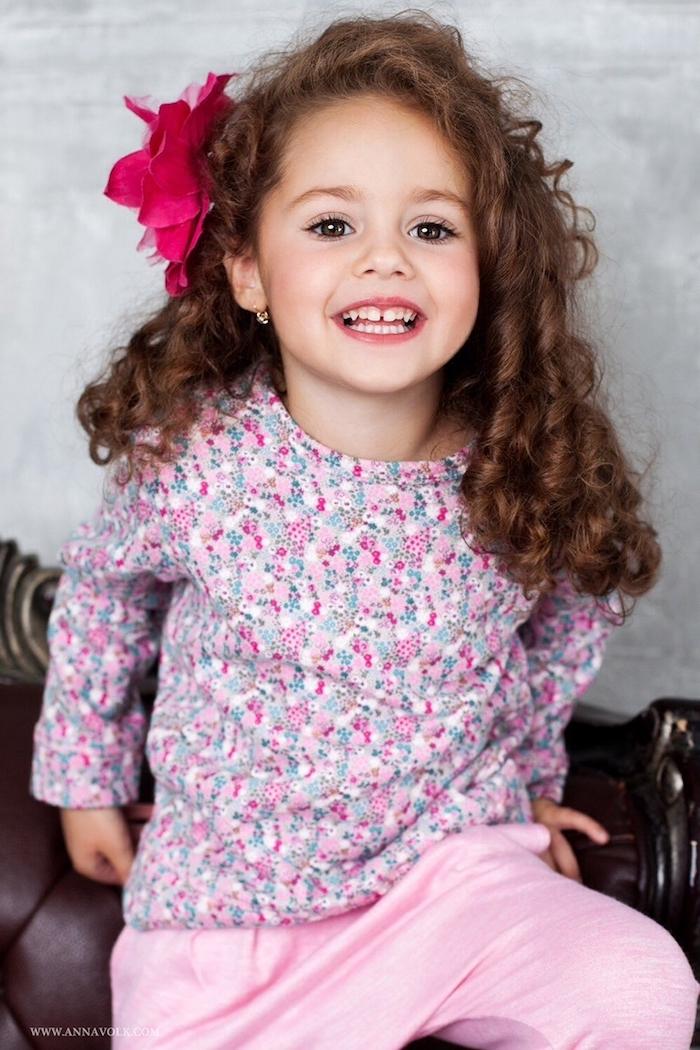 Schöne Frisuren für Mädchen, Lange lockige Haare mit Seitenscheitel, violette Haarblüte, rosafarbene Hose und Bluse mit Blumenmuster