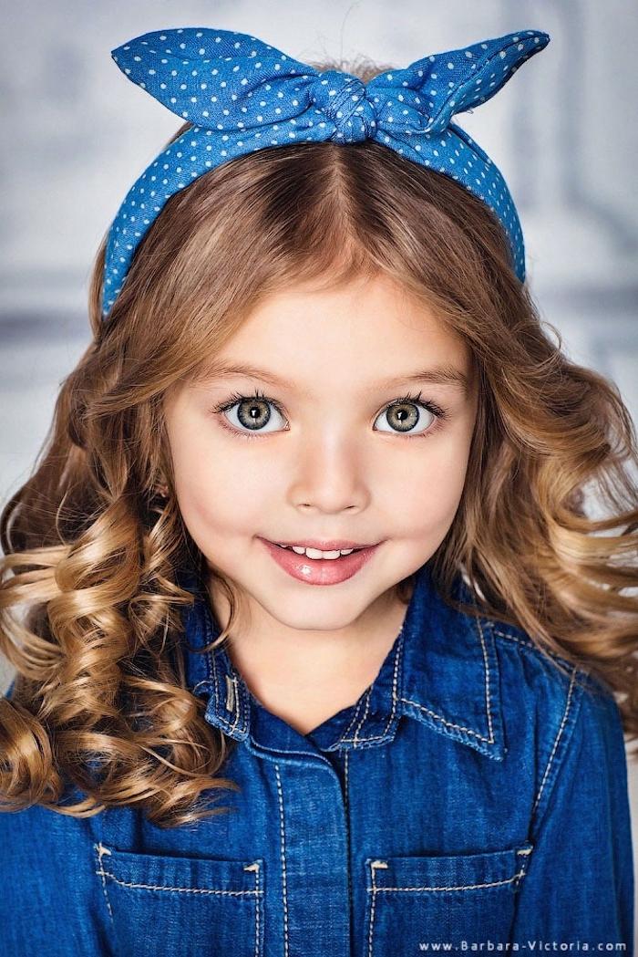 Dunkelblonde wellige Haare, Denim Jumpsuit und blaues Haarband, grüne Augen und heller Hautteint