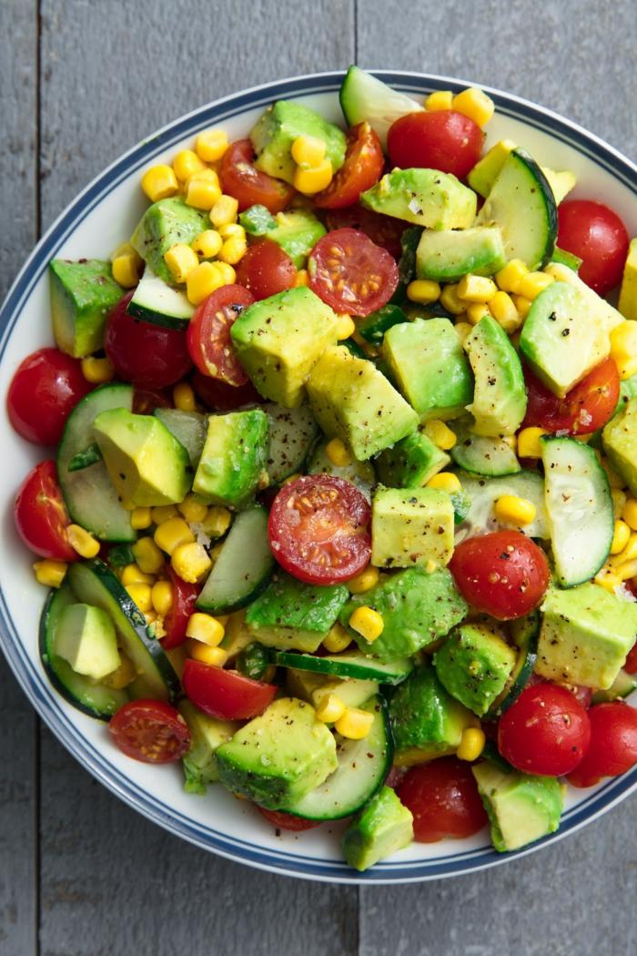 Avocado Tomaten Salat mit Kirscherbsen und Mais, kleine Gurken in einer weißen Schale