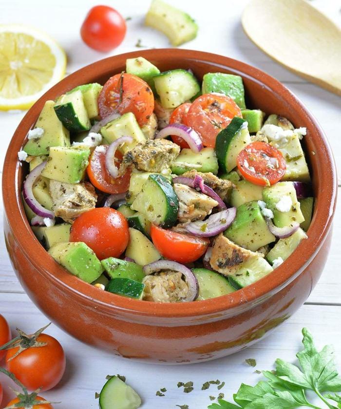 Avocado Tomaten Salat, roter Zwiebel, grüne Gurken, Kirschtomaten in einer braunen Schale