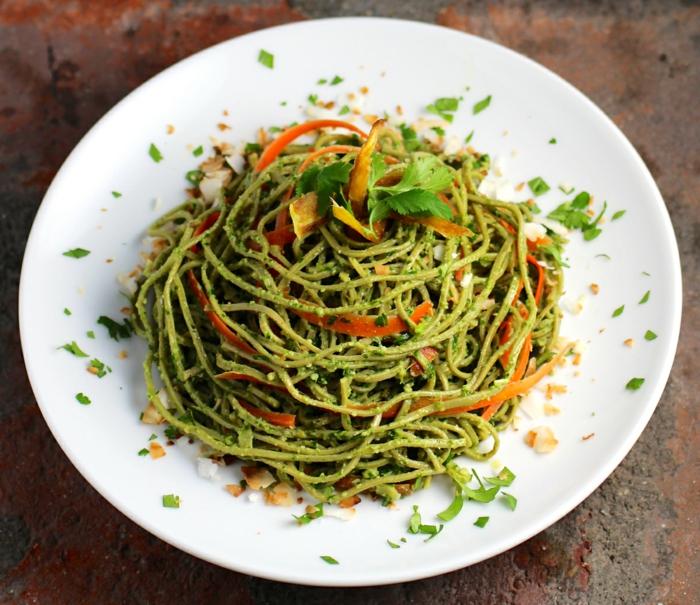 ein vegan Gericht, grüne Nudeln mit Pestosoße, Karoten auf Scheiben, Fitness Gerichte