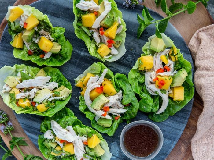 Happen, gelbe Stücke Mango und Avocado, Fleisch auf Salatblättert