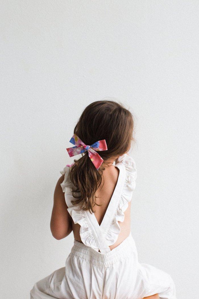 Hochzeitsfrisuren und Outfits für Mädchen, weißer Jumpsuit, locker gebundene Haare, bunte Schleife