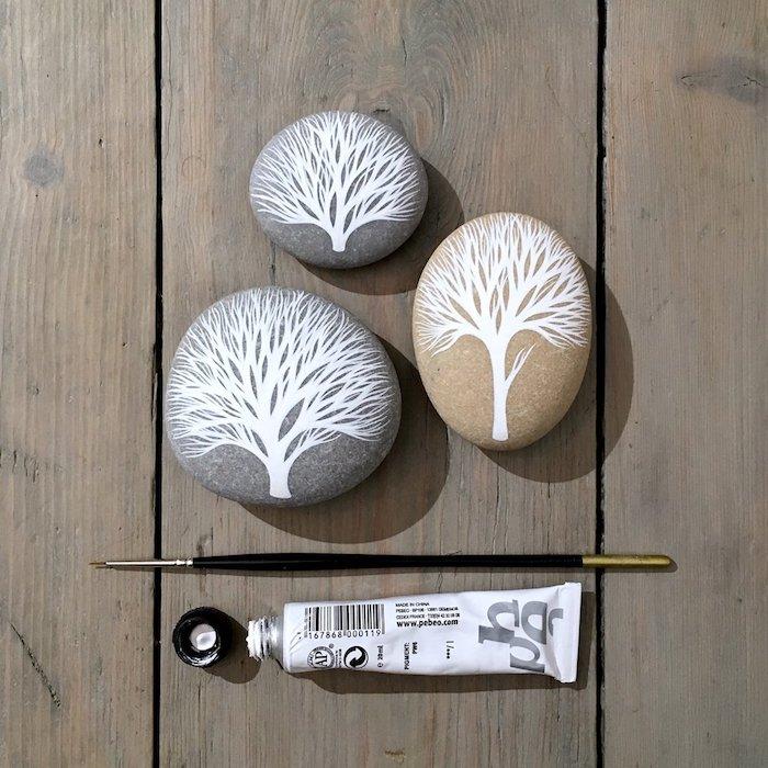 Kleine Steine mit weißer Farbe bemalen, Bäume zeichnen, schöne DIY Idee