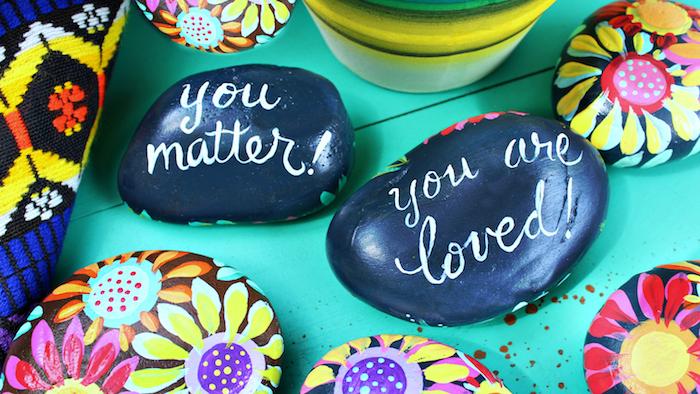 Steine mit personalisierter Botschaft beschriften und mit Blumen dekorieren