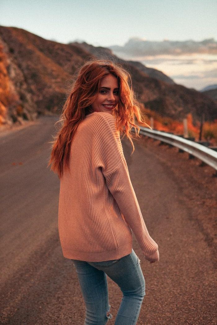 Lange kupferfarbene Haare, rosafarbener Pullover und Jeans, natürlicher Look