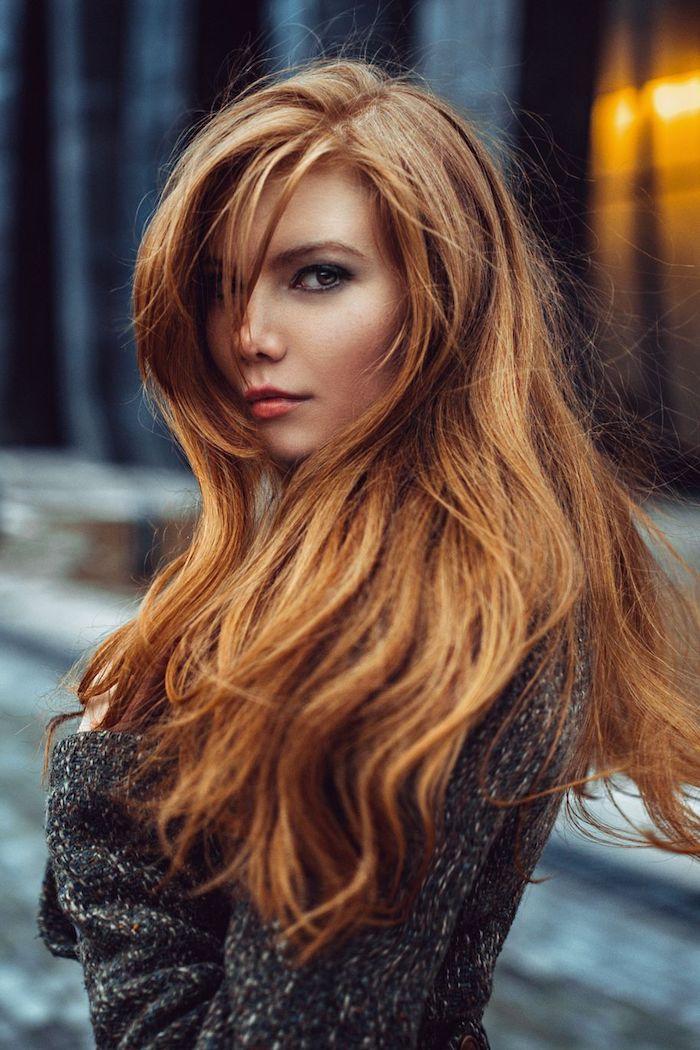 Kupferfarbene lange Haare mit Seitenscheitel, schwarzer Mantel, leichtes Make-up