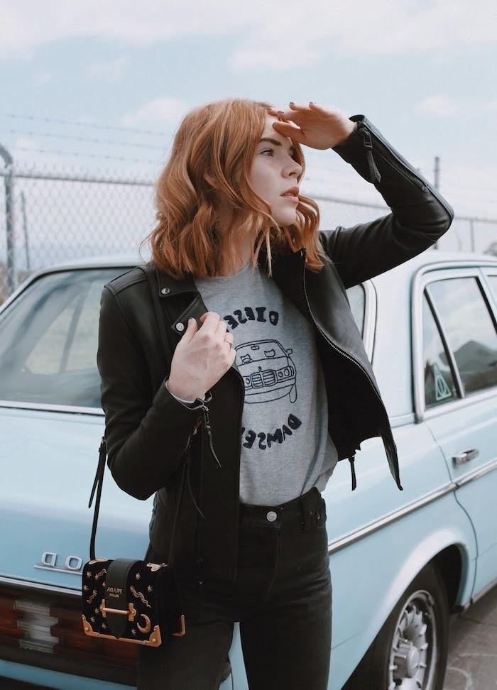 Schulterlange kupferfarbene Haare mit Mittelscheitel, schwarze Lederjacke und Hose, graues T-Shirt