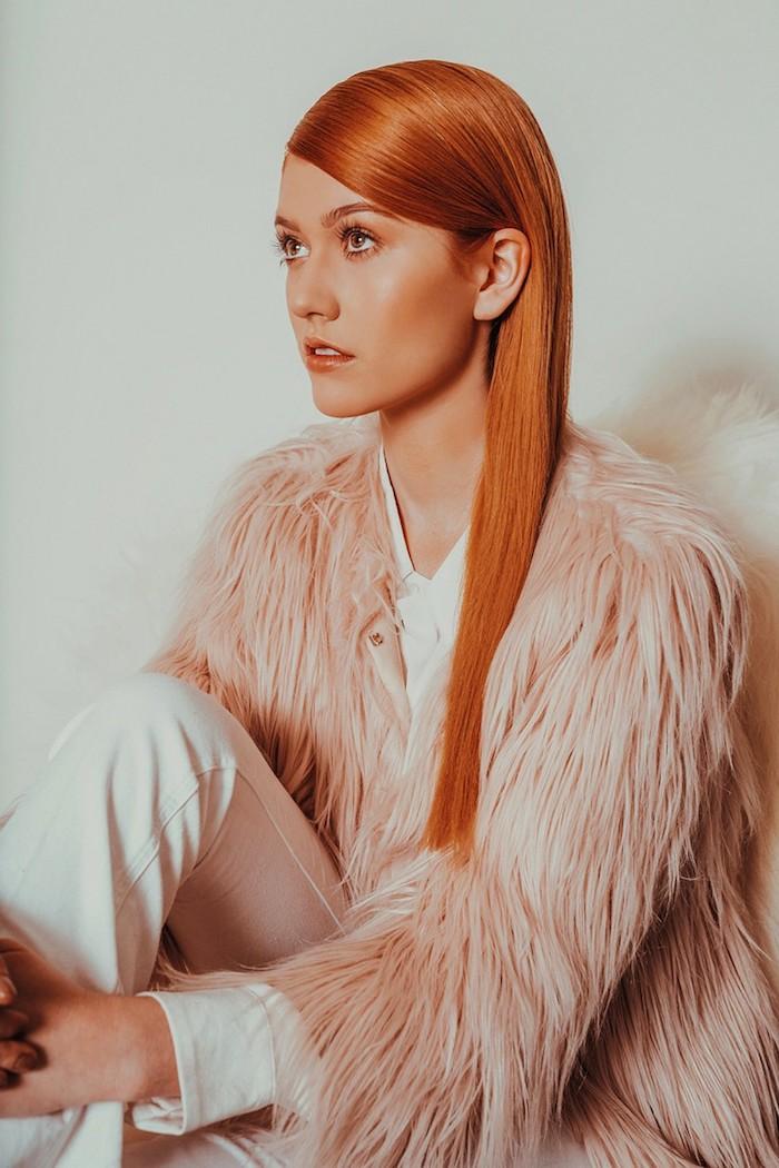 Kupfer Haarfarbe, lange glatte Haare, leichtes Tages Make-up, rosafarbener Pelzmantel und weiße Hose